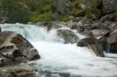 Gebirgsschneller Fluss in Norwegen unter Flusssteinen stockbild