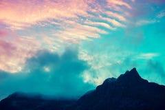 Gebirgsspitze umrissen mit bewölktem Sonnenunterganghimmel Stockbild