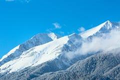 Gebirgsspitzen und blauer Himmel mit Wolkenhintergrund lizenzfreie stockfotografie