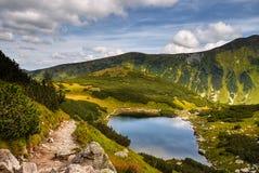 Gebirgsspur, szenische Landschaft, blauer See Lizenzfreies Stockbild
