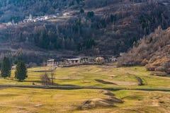 Gebirgsstadt und sonnige Frühlingswiese in den italienischen Alpen, Trentino, Italien lizenzfreie stockbilder