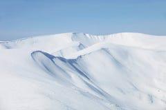 Gebirgssteigungen umfaßt mit Schnee stockfotografie