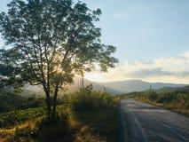 Gebirgsstraße in den Strahlen der untergehenden Sonne stockfoto