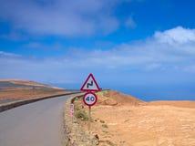 Gebirgsstraße im blauen Himmel gegen einen Hintergrund von Ozean 60 MPH Lizenzfreie Stockbilder
