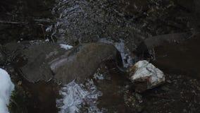 Gebirgsstrom im Wald mit Wasserfall und Schnee stock video