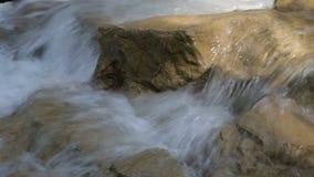 Gebirgsstrom, kleiner Wasserfall, der über Felsen mit Ton fällt stock footage