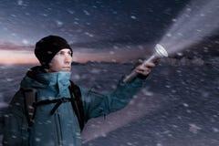 Gebirgstourist mit einer Laterne in der Hand, welche die Weise in der Dunkelheit der Nacht beleuchtet Lizenzfreies Stockbild