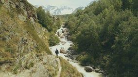 Gebirgstouristisches Gehen entlang schnelle Flussrückseitenansicht Wandern des Berges lizenzfreies stockbild