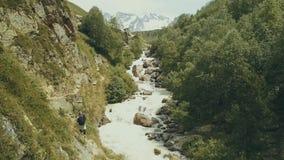Gebirgstouristisches Gehen entlang schnelle Flussrückseitenansicht Wandern des Berges lizenzfreie stockfotos