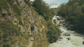 Gebirgstouristisches Gehen entlang schnelle Flussrückseitenansicht Wandern des Berges stockfotografie