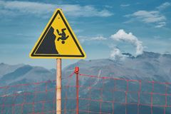 Gebirgswarnschild über das Klippenfallen Extrem trägt Gefahrenkonzept zur Schau lizenzfreie stockfotos