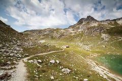 Gebirgsweg zur Kabine durch See Lizenzfreie Stockfotografie