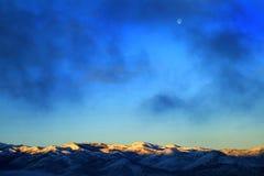 Gebirgszug im Winter-Schnee mit einer Kappe bedeckt mit Sonnenlicht und Mond Stockbilder