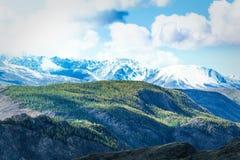 Gebirgszug mit schneebedeckten Spitzen unter den Wolken lizenzfreie stockbilder