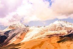 Gebirgszug mit schneebedeckten Spitzen unter den Wolken stockfotografie