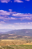 Gebirgszug mit schneeweißen Wolken auf einem blauen Himmel Lizenzfreies Stockbild