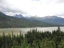 Gebirgszug mit Wäldern und Strom Üppiger mäßiger Regenwald in Alaska mit Wolken und Sonne stockfotografie