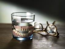 Gebisse in einem Glas Wasser Stockbild