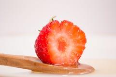 Gebissene Erdbeere im Honiglöffel Stockbild