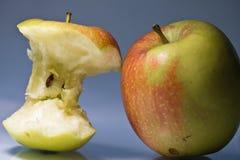 Gebissener Apfel mit traurigem Gesichtsausdruck neben glücklichem ganzem neuem Apfel metaphore Stockfotos
