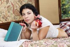 Gebissener Apfel und Blick der Frau Griff fraglich Stockfotos