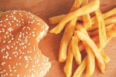 Gebissener Burger und Pommes-Frites auf einem hölzernen Brett lizenzfreie stockbilder