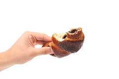 Gebissenes appetitanregendes Hörnchen mit Mohnblume. Lizenzfreie Stockfotografie