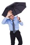 Geblendeter Geschäftsmann, der seine Augen mit seiner Hand schützt Stockfotos