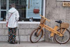 14 07 2017 geblutet, Slowenien Eine ältere Frau überprüft hölzerne Produkte eines Geschäftsfensters von einem Baum stockbilder