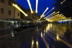 Gebogen gevolgen met regen en straatlantaarns Stock Afbeeldingen
