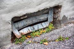 Gebogen kelderverdiepingsgrating en barst in asfalt stock afbeeldingen