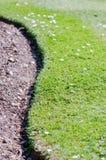 Gebogene Grasgrenze eines leeren Blumenbeets Lizenzfreie Stockbilder