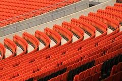 Gebogene Reihen von orange Stadionssitzen stockbild