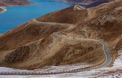 Gebogene Straße auf dem Berg neben Yamdrok See Stockbilder