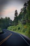 Gebogene Straße im Wald mit dunkler Vignette stockfotos