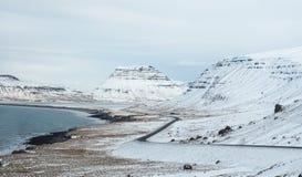 Gebogene Winterstraße mit Berg auf der Seite der Straße bedeckt Stockbilder