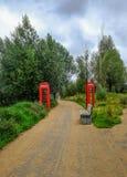 Gebogener Weg im Olympiapark mit Bank und roter Telefonzelle Lizenzfreie Stockbilder