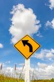 Gebogenes Straße Verkehrszeichen herein Ackerland mit bewölktem blauer Himmel backgr Lizenzfreies Stockbild