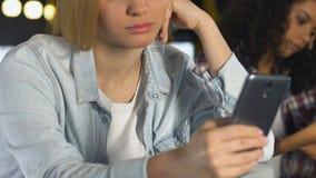 Gebohrte Damen, die auf Smartphones in der Stange, Mangel an Kommunikation in einer Liste verzeichnen und plaudern stock video