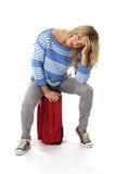 Gebohrte deprimierte junge Frau, die auf einem roten Koffer sitzt Lizenzfreies Stockfoto
