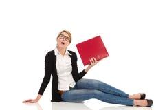Gebohrte Frau, die auf dem Boden mit Ringmappe sitzt. Lizenzfreies Stockfoto