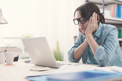 Gebohrte Frau, die mit ihrem Laptop arbeitet Stockfotos