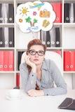 Gebohrte Geschäftsfrau, die über Feiertag im Büro träumt Stockbild