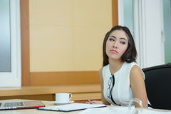 Gebohrte Geschäftsfrau, die ihrem Schreibtisch sehr langweilig betrachtet Stockfotografie