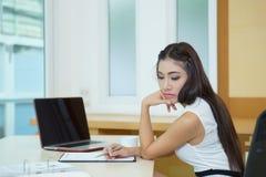 Gebohrte Geschäftsfrau, die ihrem Schreibtisch sehr langweilig betrachtet Stockbilder