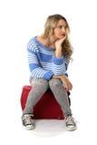 Gebohrte junge Frau, die auf einem roten Koffer sitzt Lizenzfreie Stockbilder