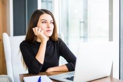 Gebohrte junge Frau im Büro, das mit einem Laptop arbeitet lizenzfreie stockfotografie