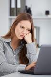 Gebohrte junge Geschäftsfrau, die mit Laptop arbeitet Lizenzfreie Stockbilder