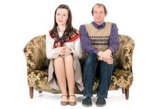 Gebohrte Paare auf Couch Lizenzfreie Stockbilder