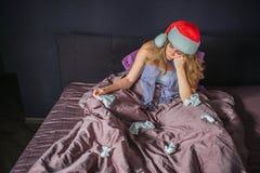 Gebohrte und kranke junge Frau im Weihnachtshut, der auf Bett sitzt und in der Hand Gewebe hält Es gibt eine anderen benutzten Se stockbild